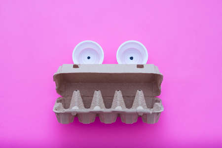 Waste management, sorting, disposal. Garbage monster created from empty plastic cups and carton egg box. Stock Photo