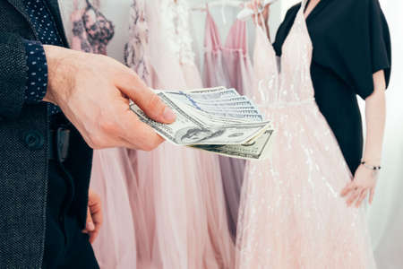 Luxury fashion boutique. Couple shopping. Rich man buying expensive evening gown for his girlfriend.