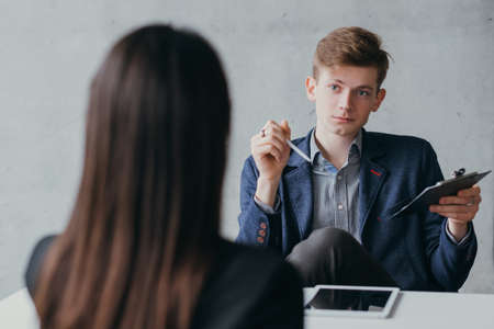 Job interview. Contemptuous young hr manager listening female applicant with sceptic facial expression.