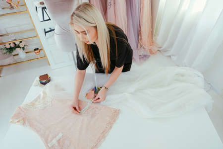 Bespoke service. Top view of female fashion designer making elegant women clothing for VIP clients. Stock Photo