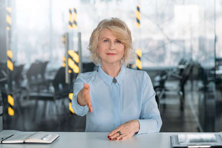Welcome team company. Assured senior business lady hand outstretched. Employment consultation partnership coaching Stock Photo