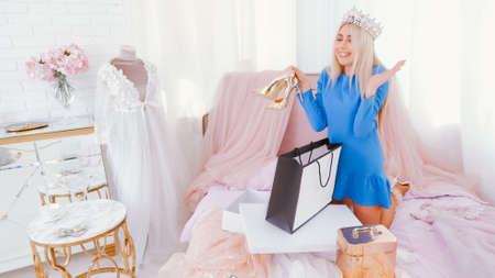 Modern princess lifestyle. Lady in tiara holding new golden shoes, happy to receive gift.