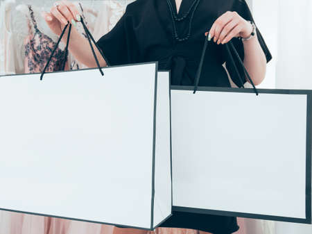 Shopping addiction. Rich woman holding two white mockup packages in luxury clothing boutique.
