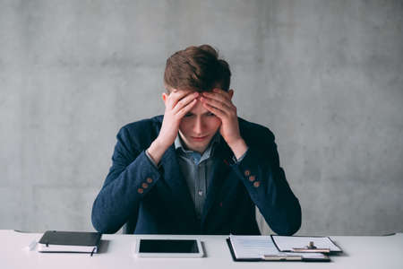 Portrait of young business man with financial problems. Guy sitting at desk, clutching his head. Stressed out facial expression.