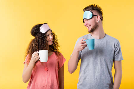 Lifestyle wake up habit. Healthy sleep good morning. Happy young couple smiling widely holding cups masks on forehead 免版税图像