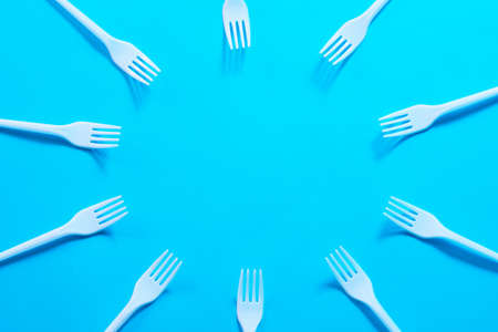Air pollution. Plastic littering. Ecology problem. White disposable forks creating circle frame on sky blue background. Copy space.