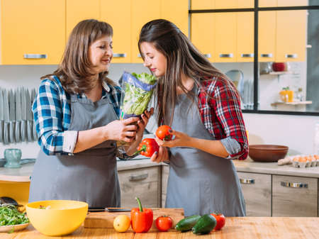Organic food trend. Vegetarian family cooking. Mother and daughter enjoying fresh lettuce flavor, making salad. Stock Photo