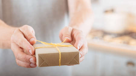 Special occasion. Closeup of handmade rustic style gift box in man hands. Blur background. Reklamní fotografie