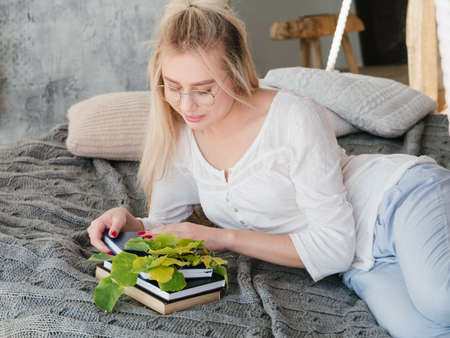 Plant biologist leisure. Portrait of female scientist in eyeglasses reading books in cozy bed at home.
