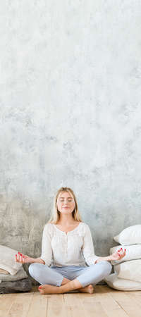 Morning meditation. Woman sitting on floor cross legged in yoga pose with mudra hands. Gray wall background. Copy space.