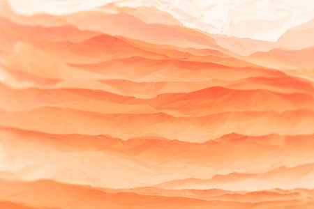 Closeup of orange crumpled paper layers stack. Abstract art background. Copy space.