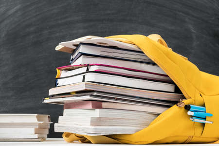 Information overload. Yellow backpack stuffed with books and note pad over empty chalkboard.
