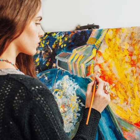 Painting process. Side view of pensive female artist creating colorful abstract artwork in studio.