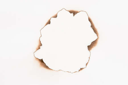 Flat lay of sheet of paper with burnt round hole on white surface. Abstract background. Frame design. Copy space.
