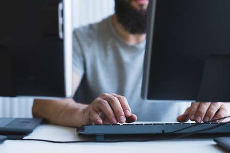 Programmation informatique. Photo recadrée d'un développeur de logiciels barbu utilisant deux moniteurs pour travailler au bureau. Banque d'images