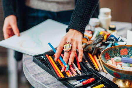 Cropped shot of female lefthanded painter artist choosing colored pencil for drawing. Фото со стока - 124624100
