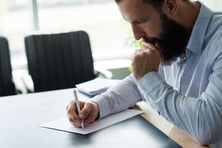Corporate life and paperwork. Side view of concerned business man writing letter. Blur office background. Copy space.