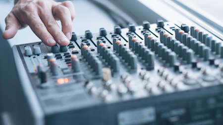 Professional sound console. Closeup of man hand mixing tracks, adjusting tune effects.