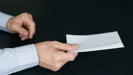 Mail delivery service. Cropped shot of man passing envelope with letter over dark background. Copy space. Stock Photo