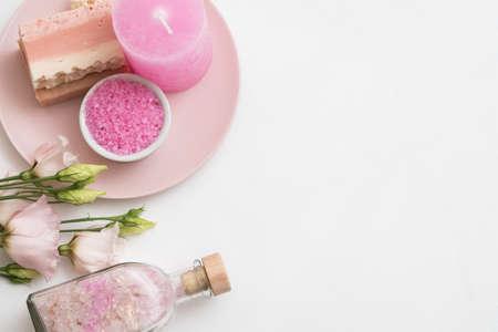 Aromatherapie im Spa. Flaches rosa Badesalz, handgemachte Seife, Kerze und Rosen auf dem Teller. Weißer Hintergrund. Platz kopieren.