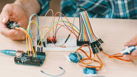 Electronic engineering experiment. Cropped shot of technician testing new invention at lab. Фото со стока