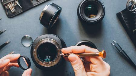 Disassembled device analysis. Top view of man hands repairing photo camera optical dslr lens.