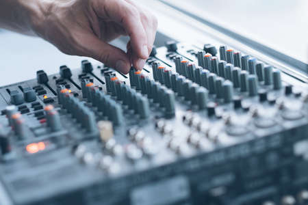 Sound recording and audio production studio. Closeup of man hand mixing tracks, adjusting tune effects. Stock Photo