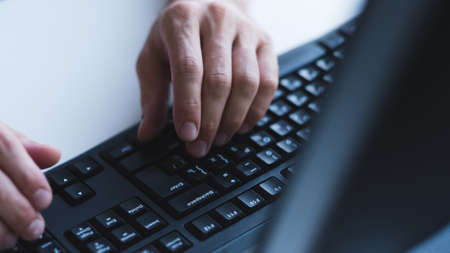 Computer programming. Coder at work. Closeup of male hands using black keyboard, typing.