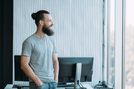 Information technology. Portrait of successful system administrator standing at workplace, looking out window, smiling. Copy space.