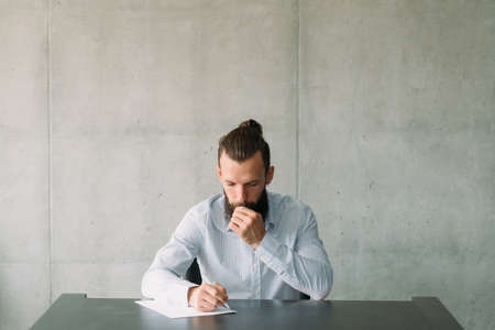 Corporate life and paperwork. Confused business man writing letter. Gray wall background. Copy space.