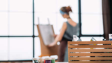 Fine art hobby. Closeup of painter tool box. Back view of lady drawing. Blur background. Copy space. Stock Photo