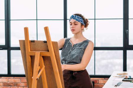 Fine art school. Inspired female painter using easel, creating artwork in modern workshop. Window background.