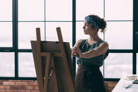 Fine art school. Young lady learning how to paint, using easel. Window background. Copy space.