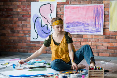 Hobby and recreation. Female artist sitting on floor, painting abstract artworks. Stock Photo