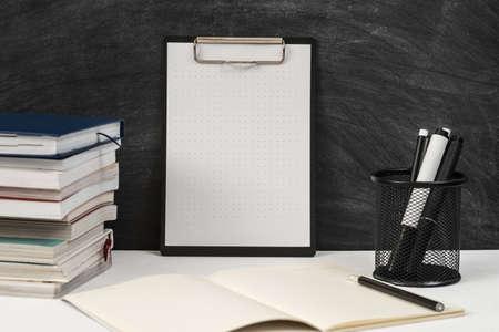 Teacher workplace. Books, mockup clipboard, stationery on desk over black empty chalkboard. Copy space. Stock Photo