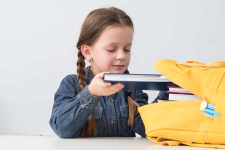 Primary education. Portrait of cute school girl packing books into yellow backpack. White background.