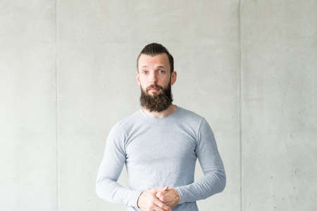 Portrait of sceptic bearded hipster guy with disappointed facial expression. Gray wall background. Copy space.