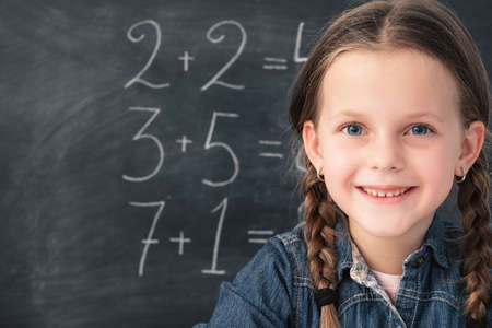 Math class. Smart smiling young girl with happy facial expression over chalkboard background with sums. Imagens
