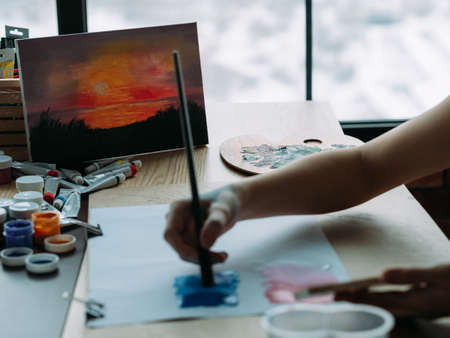 Nature view painting. Cropped shot of talented female artist creating landscape artwork in studio.