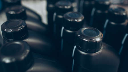 Auto detailing supplies showcase. Closeup of black plastic bottles with motor oil. Stockfoto