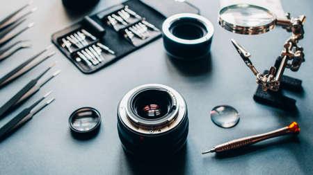 Engineer workshop. Top view of photo camera optical dslr lens and repair tool set. 版權商用圖片