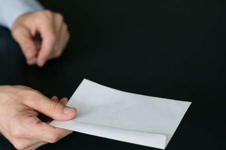 Mail delivery service. Man receiving written notice, holding white mockup envelope over dark background. Copy space. Stock Photo
