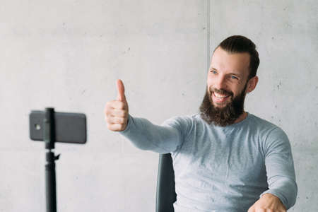 Social vlog. Bearded man using smartphone on tripod to encourage subscribers with thumb up gesture. Copy space.