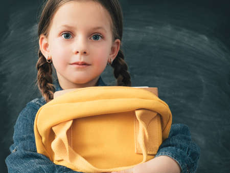 Back to school. Portrait of young girl with curious facial expression, holding yellow backpack. Chalkboard background.