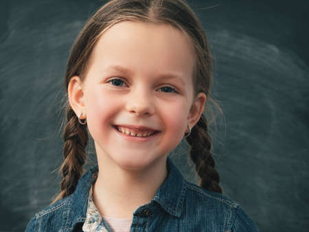 Back to school. Portrait of young smiling girl with happy facial expression over chalkboard background. Фото со стока