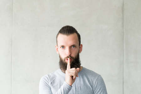 Keep silence. Portrait of sceptic bearded hipster guy warning with quiet gesture. Gray wall background. Copy space.