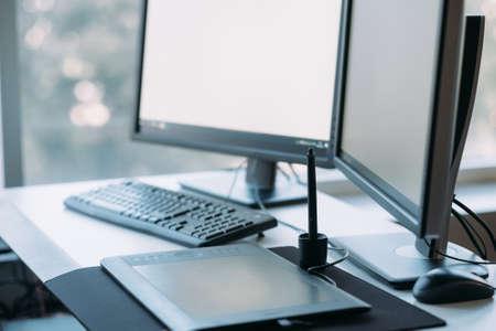 Web graphic design. Creative 3D artist workplace. White mockup monitor screen, tablet, keyboard on desk. Blur window background.