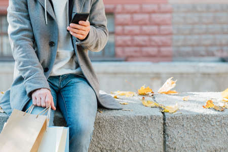 Autumn shopping. Cropped shot of man sitting on wall with packages, using smartphone. Fall urban background. Copy space.