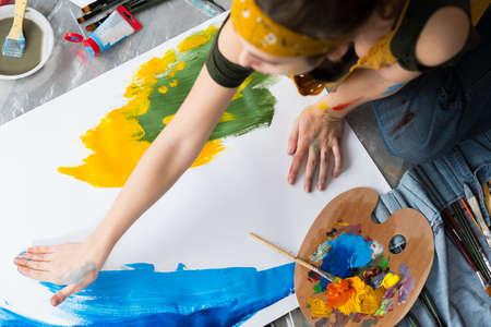 Passe-temps de peinture au doigt. Vue de dessus d'une artiste féminine assise sur le sol, utilisant des couleurs bleues et jaunes pour créer des œuvres d'art abstraites. Banque d'images