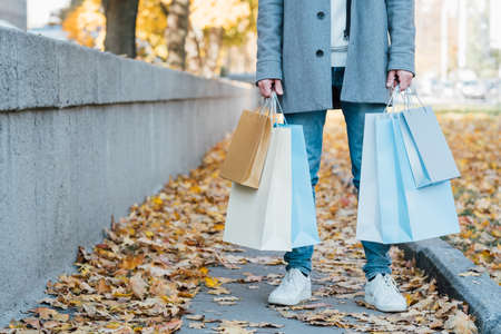 New season shopping. Cropped shot of man standing with shopping bags on fall sidewalk covered with yellow leaves. Copy space.